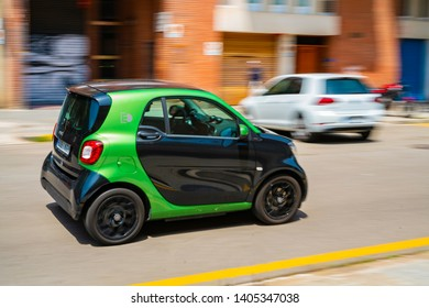 Barcelona / Spain 05 18 2019: Small car is driving along a narrow street. illustration for news about parking problems, congestion, traffic jams. Small car on narrow street.