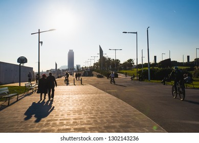 Barcelona, Spain - 05.12.2018: Beautiful sunny day with people cycling and walking along a street close to the beach