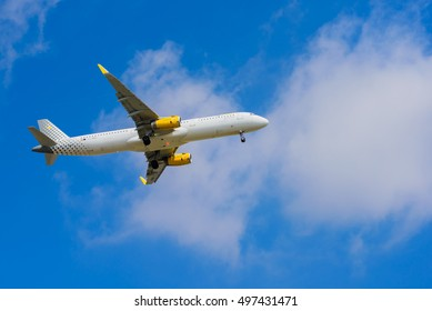 BARCELONA, SPAIN -08/20/2016: Airplane Vueling is flying to the arraval over Barcelona. Blue sky.