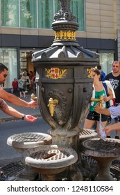 Barcelona, Spain, 08.30.2017. Cast iron drinking fountain Canaletes with bronze taps, at the beginning of the pedestrian street La Rambla on a Sunny day, surrounded by tourists gaining water