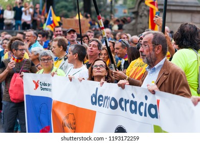 Barcelona, Spain - 1 october 2018: woman looks up at catalan flag holding democracy banner during protest for catalan independence
