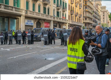 Barcelona / Spain 10 18 2019: Riots of catalan people protesting. reporters are filming a video against a background of police officers. resistance to street riots. police officers with shields.