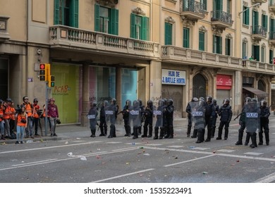 Barcelona / Spain 10 18 2019: Police officers in bulletproof vests, helmets and with shields blocked the street during riots and demonstrations. reporters are standing nearby. Riots of catalan people