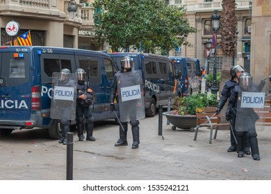 Barcelona / Spain 10 18 2019: police officers with shields and bulletproof vests stand next to police cars on the street during a riot in Barcelona. Riots of catalan people protesting.