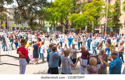 Barcelona, Spain- 10 JUNE 2018: Senior people holding hands and dancing national dance Sardana at Plaza, Barcelona, Spain. It is a type of circle dance typical of Catalonia.