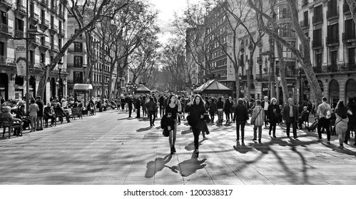 BARCELONA, SPAIN 10.02.2017.People walking by the upper section of La Rambla in Barcelona, Spain. Thousands of people walk daily by this popular pedestrian road with old buildings and stores
