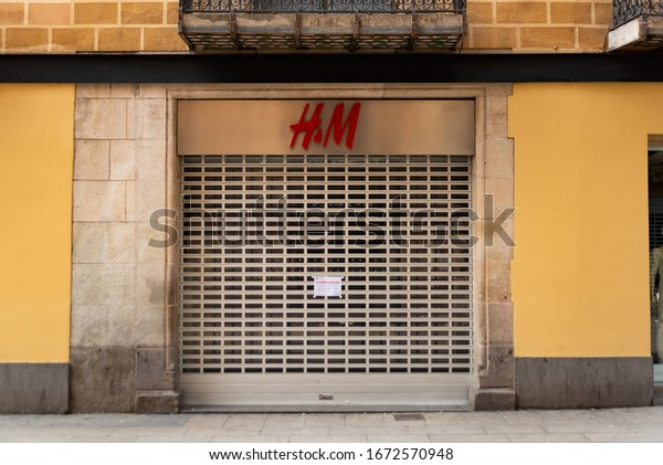 Barcelona, Spain - 14 march 2020: tourists walk past an H&M clothing shop with rolling shutter shut down because of lockdown imposed to stop the corona virus outbreak in catalonia