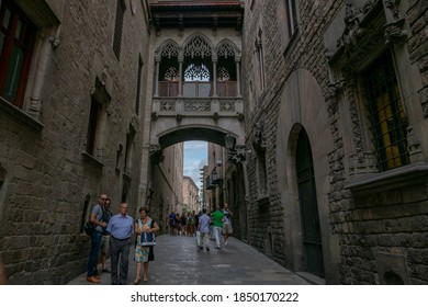 Barcelona, Spain, 14 September 2015:  neogothic bridge at Carrer del Bisbe (Bishop Street) - picture in artistic retro style. Unkonwn people pass under of this bridge every day