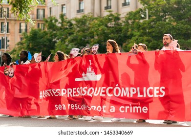 Barcelona, spain- 17 july 2019: young european women march holding banner in  protest against immigration policies and in support of ngo in the mediterranean sea