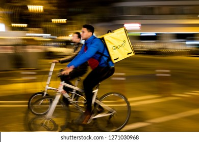 Barcelona, Spain - 21 december 2018: young riders working for Glovo delivery service riding bike in the city at night. Food delivery plays a mayor role in the new gig economy.