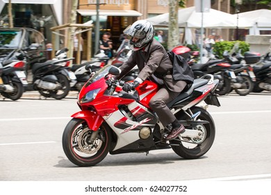 BARCELONA, SPAIN - 22 MAY 2013: A motorcyclists rides in city traffic, shot with motion blur