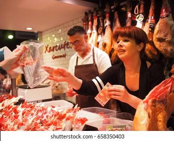 Barcelona, Spain - 29 May, 2017: A woman sells Iberico ham to customers in La Boqueria food market in Barcelona