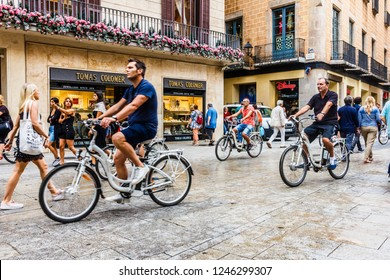 Barcelona, Spain - 4th October 2017: A tourist group on bicycles cycles down a pedestrianised shopping street. The city receives millions of tourists every year.