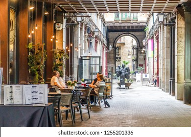 Barcelona, Spain - 4th October 2017: People drinking coffee in a restaurant in a courtyard off La Rambla. The street is  very famous pedestrianised shopping area.