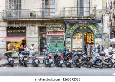 Barcelona, Spain - 4th October 2017: Motorbikes parked outside shops on Las Ramblas. The street is  very famous pedestrianised shopping area.