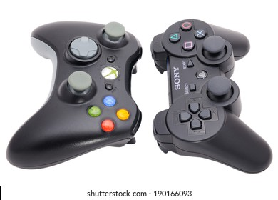 BARCELONA, SPAIN - APR 18, 2014: The DualShock 3 wireless controller, a gamepad for the PlayStation 3 in front of its big rival of Microsoft Xbox 360 Controller, isolated on white background.