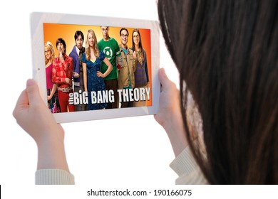 BARCELONA, SPAIN - APR 21, 2014: Unrecognizable woman watches, on her Apple Ipad, The Big Bang Theory, a famous American sitcom (situation comedy), isolated on white background.