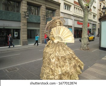 Barcelona / Spain - April 13, 2012: A street perfomer completely covered in golden paint, with a large costume ball dress and a Venetian fan