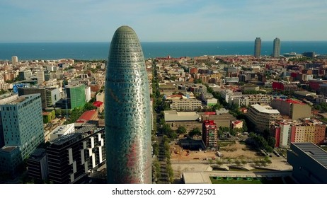 BARCELONA, SPAIN - APRIL, 15, 2017. Torre Agbar skyscraper, city and seafront aerial view on a sunny day