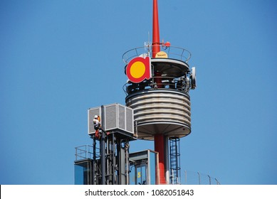 BARCELONA, SPAIN - APRIL 15, 2018: A protestor with a banner climbs a communication mast on the Arenas de Barcelona building in Placa Espanya during the Llibertat Presos Politics protest march.