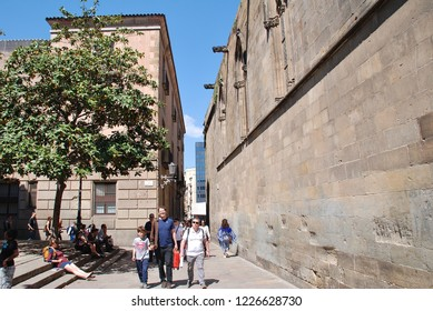 BARCELONA, SPAIN - APRIL 17, 2018: Tourists walk past the medieval Cathedral of the Holy Cross and Saint Eulalia. Construction of the main building began in 1298.