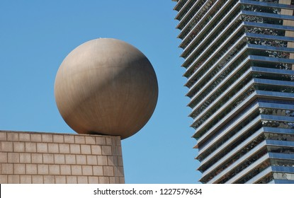BARCELONA, SPAIN - APRIL 17, 2018: The Esfera (sphere) sculpture by architect Frank Gehry at Port Olimpic with the Mapfre Tower in the background. The artwork was created in 1992 for the Olympic Games