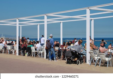 BARCELONA, SPAIN - APRIL 17, 2018: People sit at a taverna on the beach. The popular tourist destination is the Capital of Catalonia.