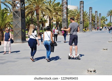 BARCELONA, SPAIN - APRIL 17, 2018: People walk and ride along the promenade at Port Olimpic. The area was re-developed for the 1992 Olympic games.