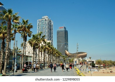BARCELONA, SPAIN - APRIL 17, 2018: People walk along the Passeig Maritim de la Barceloneta towards Port Olimpic. The twin towers of the Hotel Arts and Mapfre building are in the background.