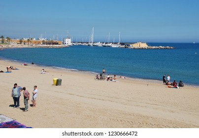 BARCELONA, SPAIN - APRIL 17, 2018: People on the sandy beach at Barcelona, Spain with Port Olimpic marina in the background.