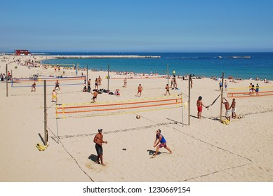 BARCELONA, SPAIN - APRIL 17, 2018: People play volley ball on the beach. The popular resort is the Capital of Catalonia.