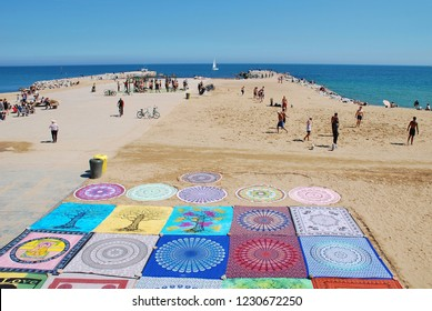 BARCELONA, SPAIN - APRIL 17, 2018: Blankets spread out for sale on the sandy beach. The popular resort is the Capital of Catalonia.