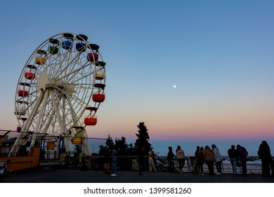 BARCELONA, SPAIN - APRIL 2017: Ferris wheel in Tibidabo with full moon in the sky. It is located at free access area of Tibidabo Amusement Park. It's the oldest amusement park in Europe, founded 1928.