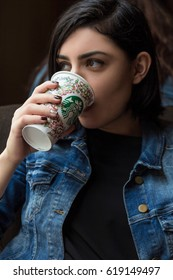 BARCELONA, SPAIN - APRIL 22, 2016: Beautiful young woman drinking coffee at Starbucks cafe in Barcelona