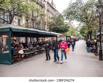 Barcelona, Spain - April 22, 2019: People are strolling along the famous Rambla Catalunya at Barcelona, Spain.