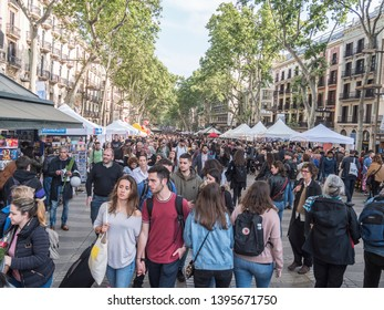 Barcelona, Spain - April 23, 2019: Thousands of people, spanish and tourists,  are strolling along the famous ramblas of Barcelona, Spain, at the day of San Jordi  (Sant George).