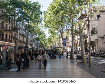 Barcelona, Spain - April 26, 2019: People are strolling along the famous Ramblas of Barcelona, Spain.