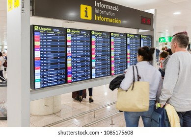 BARCELONA, SPAIN - APRIL 27, 2018: Tourists look at a flight Board in the Airport of El Prat near Barcelona in Spain
