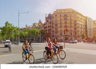 BARCELONA, SPAIN - APRIL 27, 2018: Girls ride bicycles in the center of Barcelona on the street passage de Gracia near the house of batlo