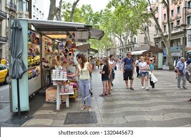 BARCELONA, SPAIN - AUGUST 08, 2015: People walk La Rambla street. La Rambla is popular tourist destination in Barcelona