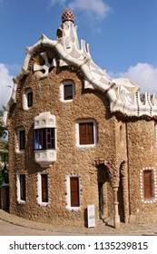 BARCELONA, SPAIN - AUGUST 11, 2007: Entrance lodge to Parc Guell designed by Antoni Gaudi, UNESCO, with a skyline view of the city of Barcelona, Catalonia, Spain