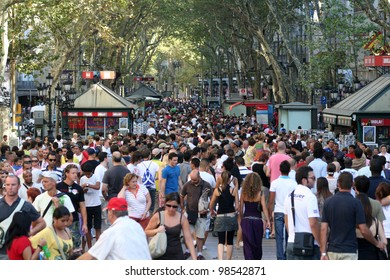 BARCELONA, SPAIN - AUGUST 14: Famous street La Rambla, August 14, 2009 in Barcelona, Spain. Thousands of people walk daily by this popular pedestrian area 1.2 kilometer long.