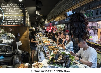 Barcelona, Spain - August 16, 2017. People eat seafood at a tapas bar inside La Boqueria public market in the Ciudad Vieja district of Barcelona.