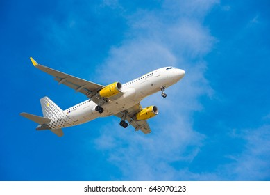 BARCELONA, SPAIN - AUGUST 20, 2016: Airplane Vueling is flying over Barcelona. Blue sky