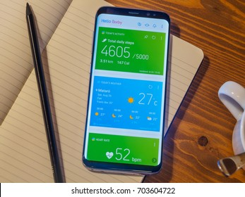 Barcelona, Spain - AUGUST 2017 :  Smartphone Samsung Galaxy S8 Plus Orchid Grey Color, initial app Bixby screen on the rustic wood background with notebook, pencil and coffee