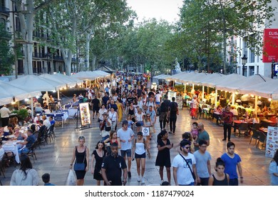 Barcelona, Spain- August 2018: People walk by at the famous La Rambla