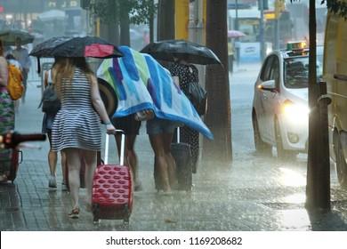 Barcelona, Spain - August 2018; Women walk under umbrella during heavy rain