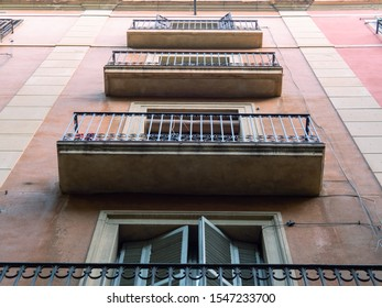 Barcelona, Spain - august 2019: pink building in city center, middle view. Balconies with black curved railing, bottom-up view. Selective soft focus. Blurred background