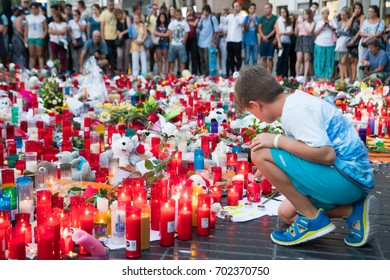 BARCELONA, SPAIN - AUGUST 21, 2017: A boy giving a tribute to the victims of Ramblas attack. August 21th, 2017 in Barcelona, Spain.
