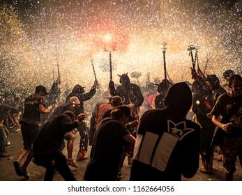 "Barcelona, Spain. August 22, 2018 - People dancing in the Fire Run ""Correfoc"" celebration in Gracia Festival in Barcelona"